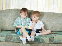 Due ragazzi leggenti. Con il libro di carta ed elettronico Fotografie Stock Libere da Diritti