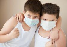 Due ragazzi positivi nelle maschere mediche Fotografie Stock Libere da Diritti