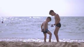 Due ragazzi stanno giocando sulla spiaggia stock footage