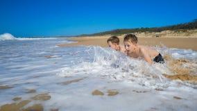 Due ragazzi sulla spiaggia che ottiene bagnata dall'onda stock footage