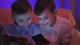 Due ragazzi svegli che giocano video gioco con lo Smart Phone all'interno video d archivio