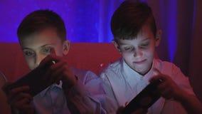 Due ragazzi svegli che giocano video gioco con lo Smart Phone nella stanza stock footage