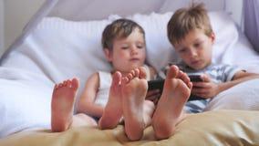 Due ragazzi svegli che prendono un resto al giorno Fuoco sui piedi dei ragazzi stock footage