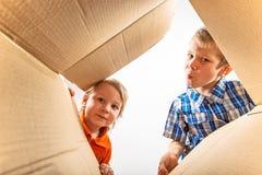 Due ragazzini che aprono scatola di cartone e sguardo Fotografia Stock Libera da Diritti