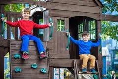 Due ragazzini che giocano insieme e che si divertono Momento della famiglia di stile di vita dei fratelli germani sul campo da gi immagine stock