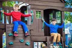 Due ragazzini che giocano insieme e che si divertono Momento della famiglia di stile di vita dei fratelli germani sul campo da gi fotografie stock