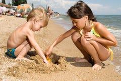 Due ragazzini che scavano sabbia alla spiaggia Immagine Stock