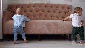 Due ragazzini si appoggiano il sofà e provano a camminare video d archivio