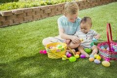 Due ragazzini svegli che raccolgono le uova su una caccia dell'uovo di Pasqua all'aperto immagine stock libera da diritti