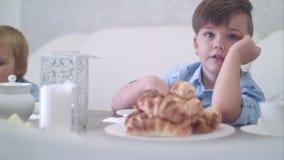 Due ragazzini svegli divertendosi alla tavola di t? con pasticceria stock footage
