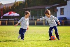 Due ragazzini svegli, giocare a calcio Fotografie Stock