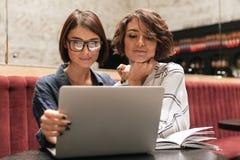 Due responsabili abbastanza femminili che si siedono dalla tavola Fotografia Stock