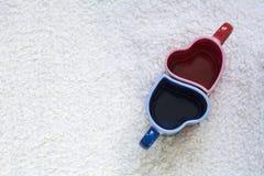 Due rossi e tazze blu nella forma di cuore Fotografia Stock