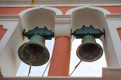 Due Rusty Antique Bells Hanging anziano dal campanile incurvato aperto della chiesa Strumento di percussione producendo suono qua immagini stock libere da diritti