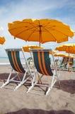 Due salotti ed ombrello giallo sulla spiaggia fotografia stock libera da diritti