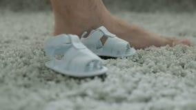 Due sandali del ` s dei bambini vicino ad un piede del ` s dell'uomo stock footage