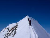 Due scalatori di montagna maschii su una cresta esposta della sommità della neve nelle alpi svizzere Fotografia Stock