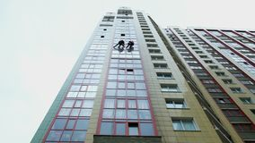Due scalatori industriali sono lavare, pulente la facciata di un edificio per uffici moderno archivi video