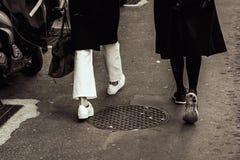 Due scarpe del ` s delle donne alla moda senza calzini sono sulla strada Genere sui vostri piedi tonalità immagine stock