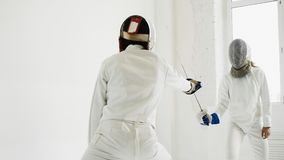 Due schermitori che hanno attacco di addestramento si esercita nel recintare lo studio Fotografia Stock Libera da Diritti