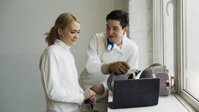 Due schermitori giovani uomo e donna che guardano recintando esercitazione sul computer portatile e condividendo esperienza prima Fotografia Stock