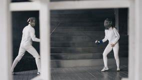 Due schermitori uomo e donna hanno recinzione della partita all'interno Fotografia Stock