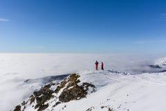 Due sciatori sopra la montagna sopra le nuvole Fotografia Stock Libera da Diritti