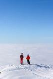 Due sciatori sopra la montagna sopra le nuvole Immagine Stock