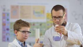 Due scienziati fa gli esperimenti con ghiaccio secco in laboratorio stock footage