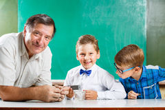 Due scolari ed il loro insegnante nella classe Fotografie Stock