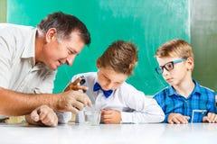 Due scolari ed il loro insegnante nella classe Immagine Stock