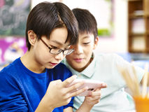 Due scolari elementari asiatici che giocano gioco con il cellulare Fotografia Stock Libera da Diritti