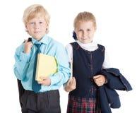 Due scolari in uniforme che sta con i manuali, fondo bianco isolato Immagini Stock