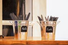 Due secchi piccoli della latta sul contatore al ristorante che tiene coltelleria di plastica - coltelli e forcelle - fuoco selett fotografie stock libere da diritti