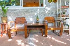 Due sedie di legno d'annata sul portico del cemento e sulla parte anteriore lucidata della parete del cemento della casa fotografia stock libera da diritti