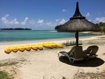 Due sedie ed ombrelli con le canoe gialle alla spiaggia Immagini Stock Libere da Diritti