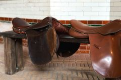 Due selle di cuoio del cavallo sul banco nella stalla fotografia stock libera da diritti