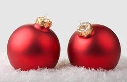 Due sfere rosse di natale su neve Immagini Stock