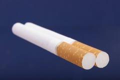 Due sigarette su fondo blu Immagine Stock