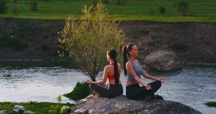 Due signore degli amici alla natura nel posto di stupore con un lago meditazione di pratica di yoga posano sull'le grandi pietre  video d archivio