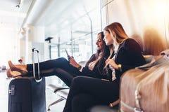 Due signore di affari che esaminano telefono cellulare mentre aspettando il volo in terminale dell'internazionale dell'aeroporto Fotografia Stock