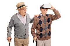Due signori senior che per mezzo di una cuffia avricolare di VR Fotografie Stock