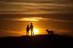 Due siluette di un bambino al fondo di tramonto fotografie stock