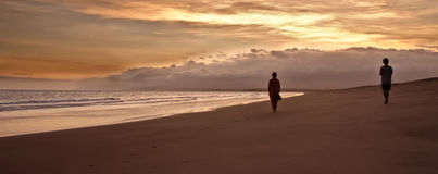 Due siluette vaghe che camminano su una spiaggia Immagine Stock
