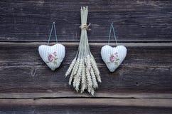 Due simboli dei cuori del panno e mazzi delle orecchie del grano sulla parete Fotografia Stock