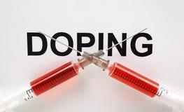Due siringhe hanno riempito di verniciatura liquida rossa di parola scritta in lettere maiuscole nel fondo Immagine Stock