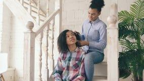 Due sistres ricci afroamericani delle ragazze rendono a divertimento l'acconciatura riccia e si divertono a casa stock footage