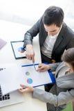 Due soci commerciali che analizzano un rapporto Immagini Stock