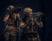 Due soldati delle forze speciali in attrezzatura protettiva piena che tiene i fucili di assalto e che punta sugli obiettivi Foto  fotografia stock libera da diritti