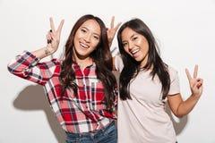 Due sorelle abbastanza allegre delle signore dell'asiatico che mostrano la pace gesture immagini stock